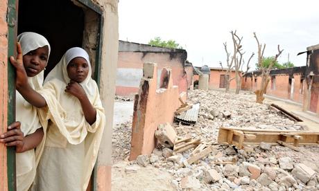 Schoolgirls stand in a Maiduguri classroom burnt by Boko Haram in May
